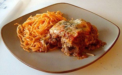 Meatloaf Parmesan on plate with spaghetti noodles