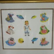 Gold frame with paper doll and doll clothing.