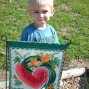 Small boy standing behind a garden flag.