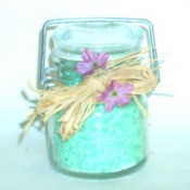 A jar of turquoise colored homemade bath salts.