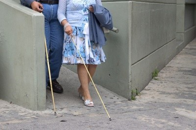 Blind man and woman walking down a ramp.