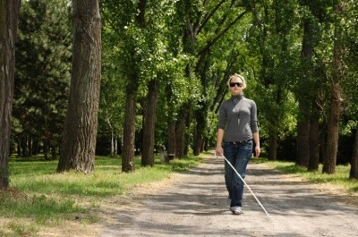 Blind woman walking in a park