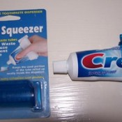 A tube of toothpaste with a tube squeezer.