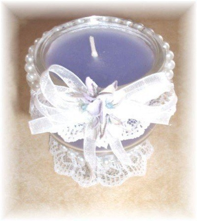 Decorated candle in glass stemmed dish.