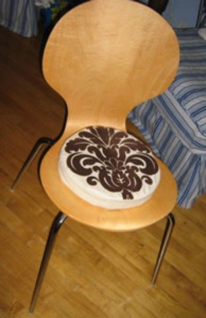 Circular pad on wooden chair.