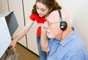 a girl and a sight impaired man using assistive technology.