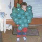Little boy dressed as a bunch of grapes.