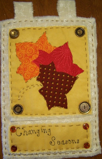 Decorative tabbed quilt with fall motif.