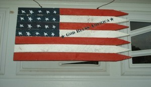 Stylized American flag made from fence pickets.