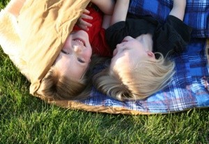 Kids in a sleeping bag on the lawn.