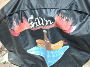 Painted design (hot dog and a soda) on black grill cover.