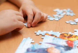 Small hands putting together a puzzle