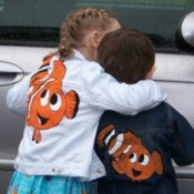 Two kids wearing jackets with an orange and white clown fish painted on them.