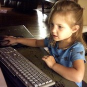 Young girl using computer mouse.