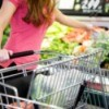 Woman and grocery shopping cart in produce aisle.