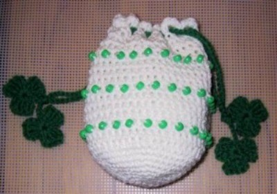 White crochet bag with green beads and shamrocks.