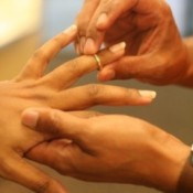 A wedding ring being placed on the ring finger.