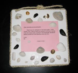 Foam board decorated with seashells and a poem or other saying.