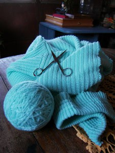 A knitted item with a ball of yarn being unraveled from it.