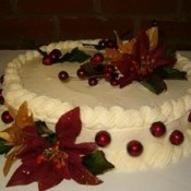 White frosted cake decorated with poinsettias.