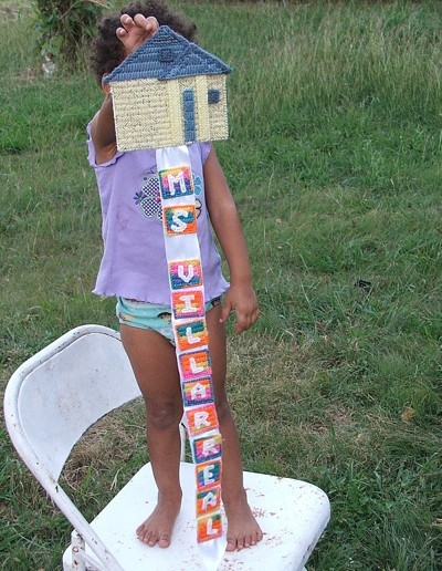 Little girl holding decoration consisting of house with blocks of letters hanging down.