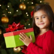 A young girl holding a gift.
