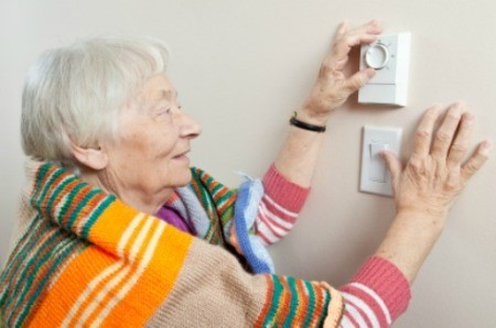 A woman adjust her heat thermostat to save money.