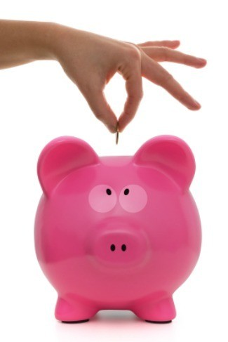 putting a penny into a pink piggy bank