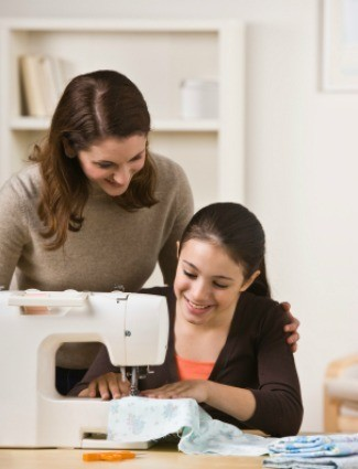 A mom teacher her daughter to sew.