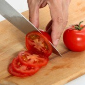 Cutting tomatoes on a cutting board.