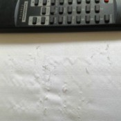 Damage to sheets next to remote for scale.