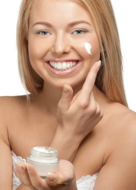 Woman putting on eye cream.