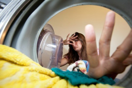 Smelling clothing in the washing machine.