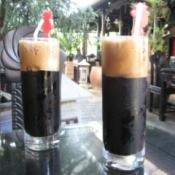 Two tall glasses of iced Vietnamese coffee.