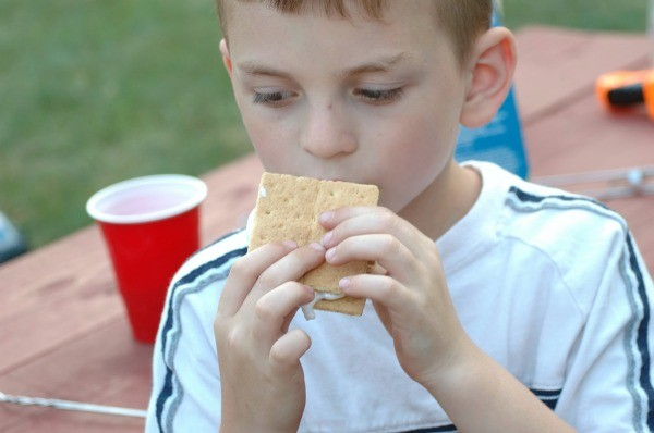 A child eating smores at a camp site.