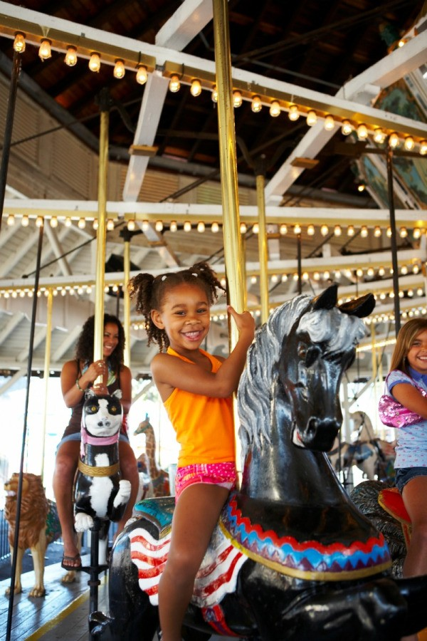 A girl on a merry go round at an amusement park.