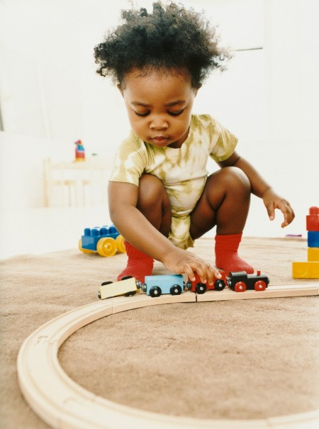 A young girl playing with a toy train.