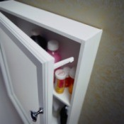 A medicine cabinet door with a child lock on it to help it stayed closed.