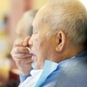 Elderly man wearing a bib while eating.