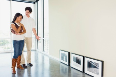 A couple looking at framed artwork in their apartment.