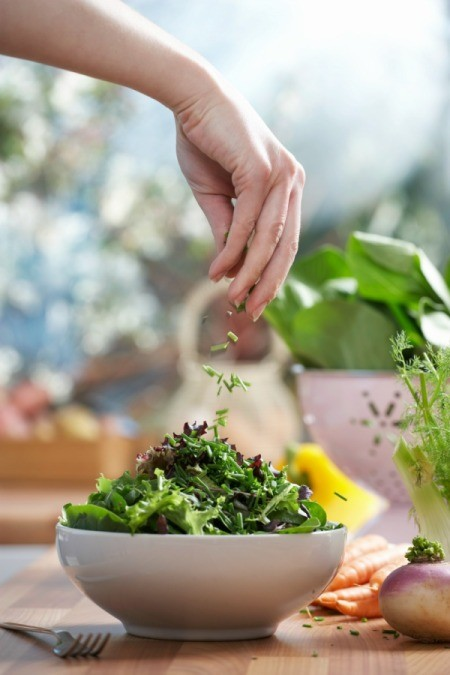 Woman Sprinkling Herbs on Her Summer Salad