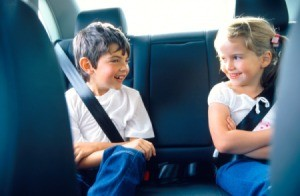 Two kids playing a game on a road trip.