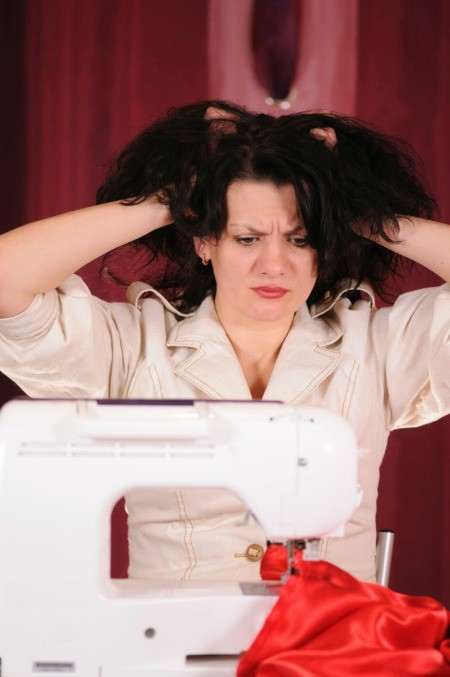 A woman getting frustrated with her sewing machine.