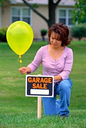 A woman putting a balloon on a garage sale sign.