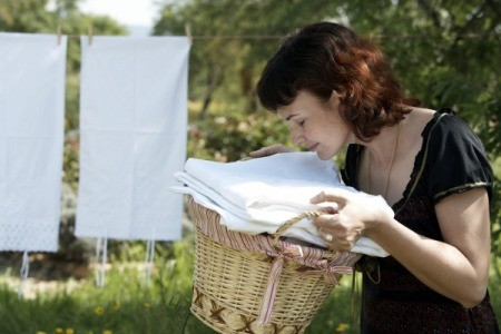 A woman smelling her fresh laundry.