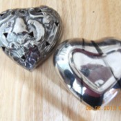 Heart shaped silver bowl and lid with a dark line from rubber band.