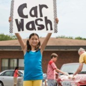 A girl holding up a car wash sign at a school fundraiser.