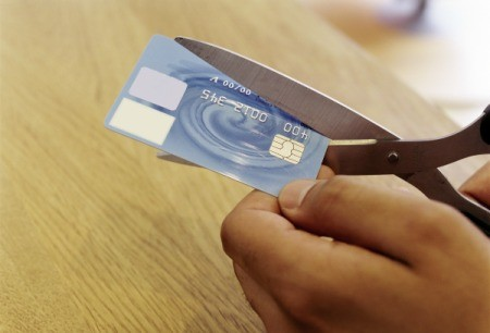 Cutting a credit card with scissors.