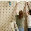 Two women removing wallpaper.
