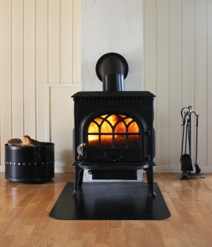 A wood stove with firelogs in it.